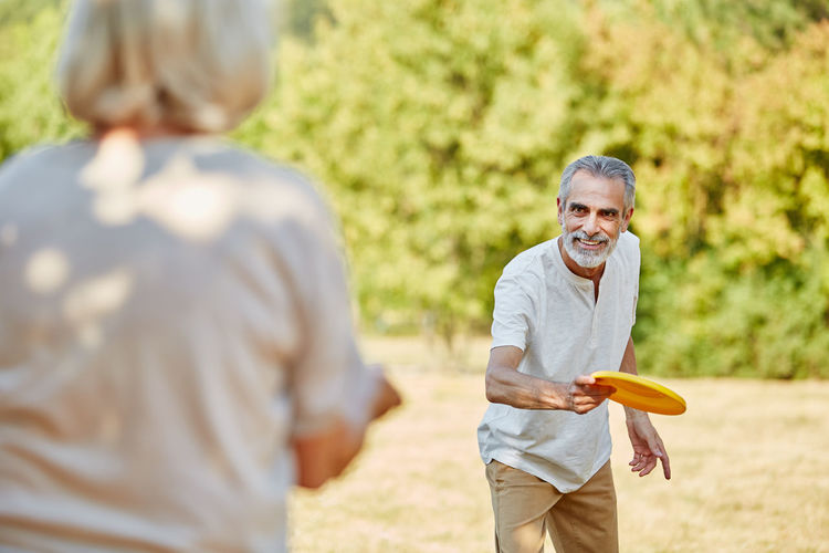 Senior Couple Playing With Plastic Disc In Park