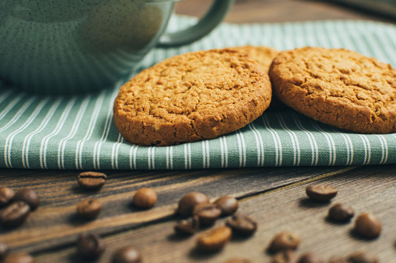 High angle view of cookies by drink in cup and beans on table