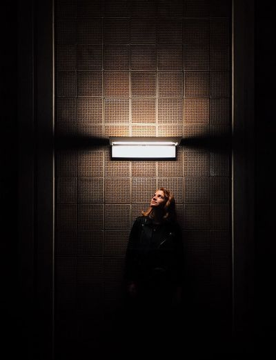 Young Woman Looking At Illuminated Neon Light Mounted On Wall