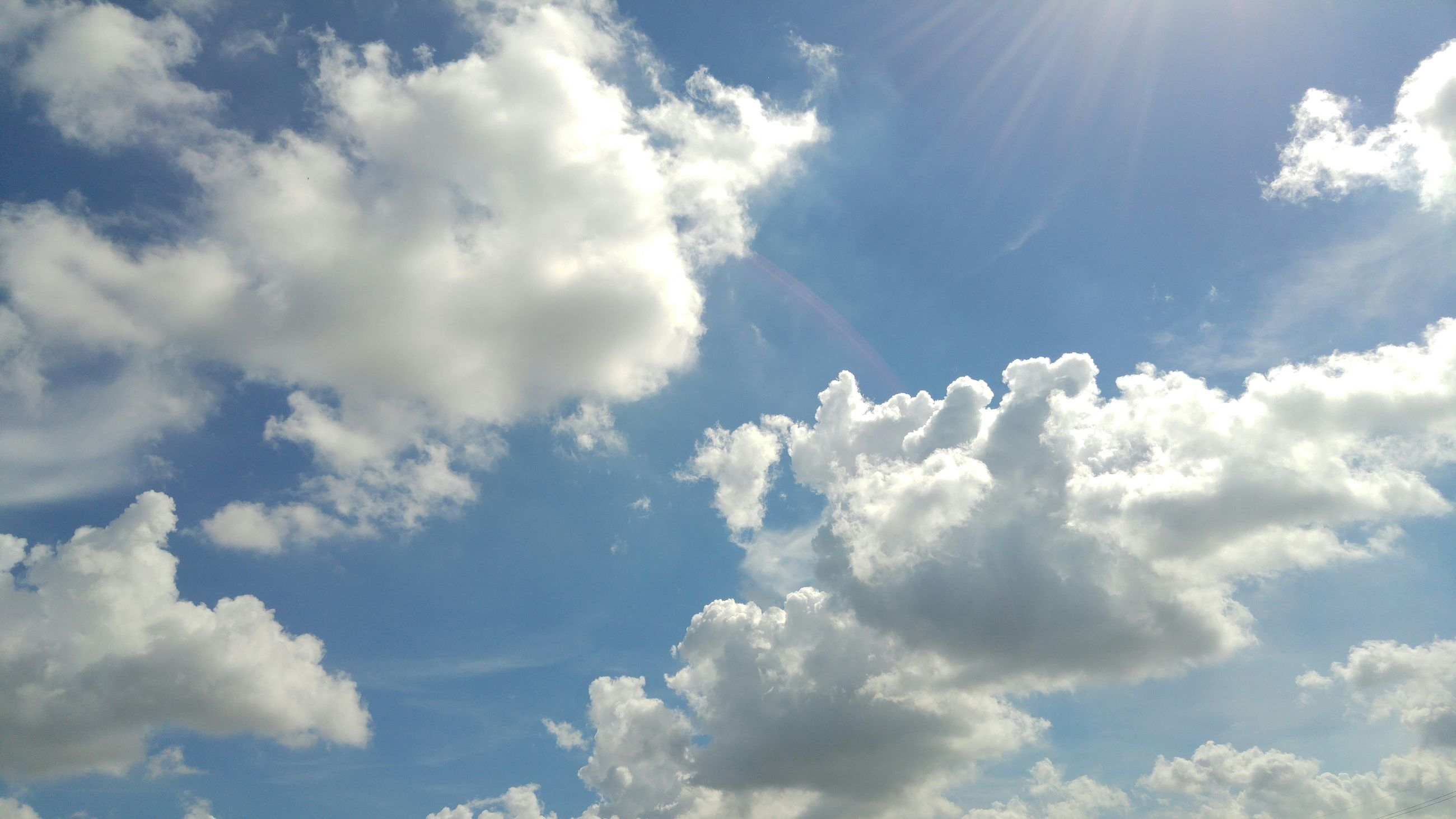 sky, beauty in nature, low angle view, cloud - sky, sky only, scenics, tranquility, blue, nature, tranquil scene, cloudscape, sunbeam, backgrounds, sunlight, cloud, white color, idyllic, cloudy, day, full frame