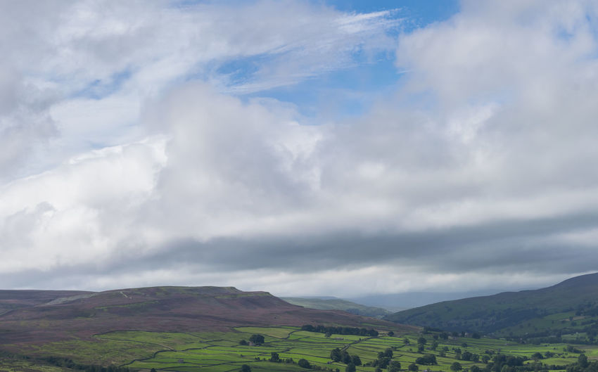 View Of Agricultural Landscape Against Cloudy Sky