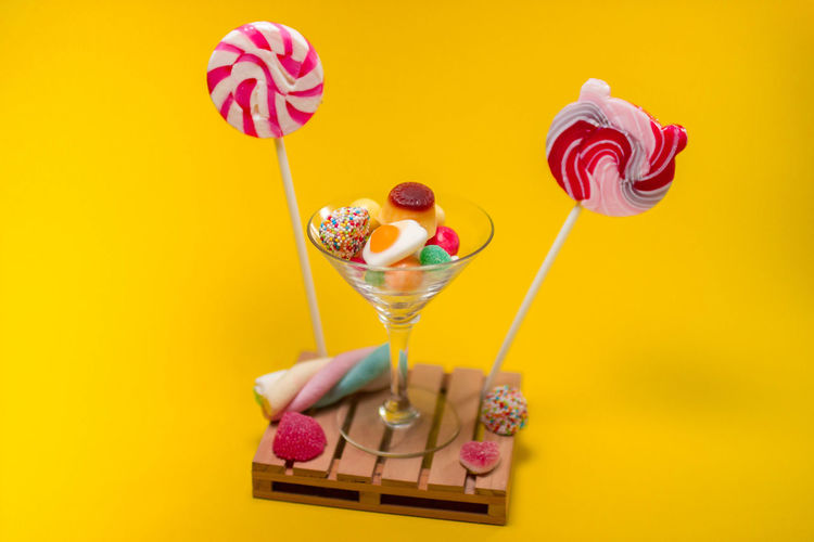 Candy Colored Background Dessert Food Food And Drink Freshness Indoors  Indulgence Lollipop No People Pink Color Red Snack Still Life Studio Shot Sweet Sweet Food Temptation Unhealthy Eating Yellow Yellow Background