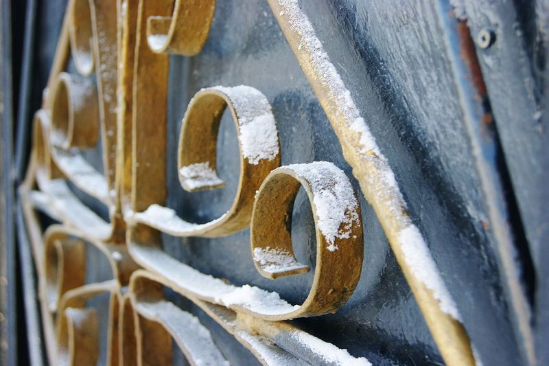 Close-up of snow on metallic fence