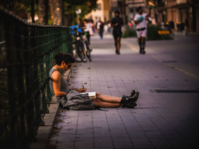 Side view of woman writing in book while sitting on footpath