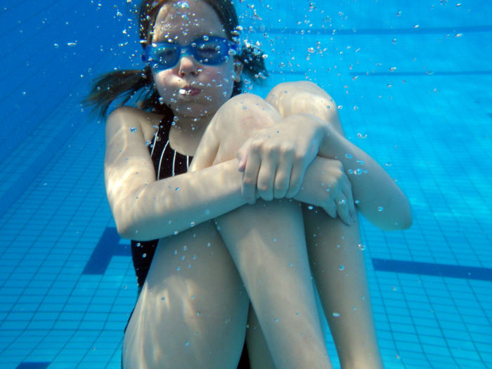 Portrait of girl with puffed cheeks in swimming pool
