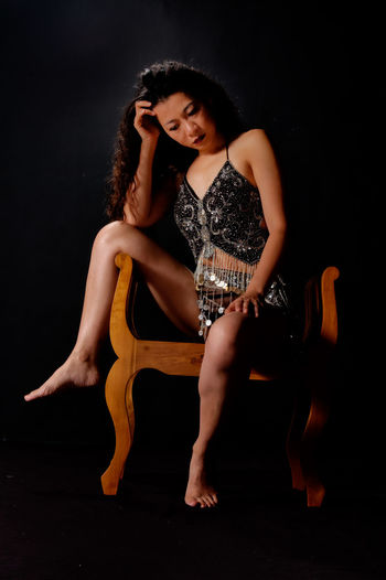 Asian Woman Chinese Women Sitting Adult Asian Women Beautiful Woman Beauty Belly Dancer Black Background Chinese Woman Chinese Woman Portrait Fashion Model Full Length Lingerie Lingerie Shoot One Person One Young Woman Only People Real People Studio Shot Wood Bench Young Adult Young Women