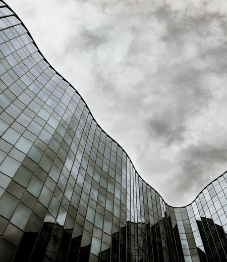 curvy exterior design of office building. Cloudy Curves Exterior Façade Architecture Black And White Building Exterior Built Structure City Darkness And Light Day Distortion Extreme Close-up Low Angle View Modern Monochrome Photography Movement No People Office Building Outdoors Reflection Sky Skyscraper Wavy Lines