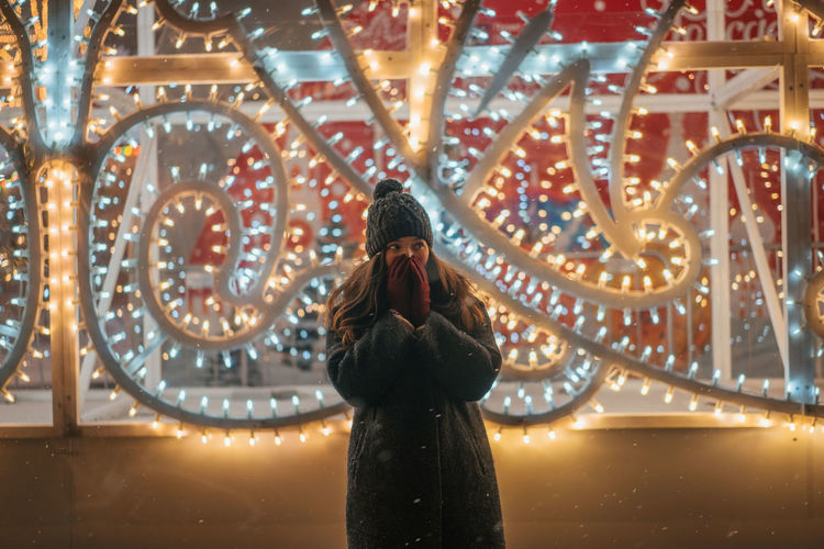 Christmas Christmas Decoration Portrait New Year One Person Real People Standing Illuminated Leisure Activity Lifestyles Adult Women Night Architecture Casual Clothing Three Quarter Length Front View Built Structure Young Women Young Adult Focus On Foreground Warm Clothing Clothing Outdoors Hairstyle Snowing