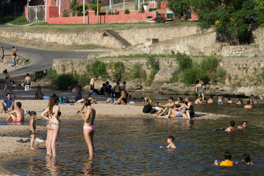Group of people enjoying a beach after a high temperature of 37 degrees in the day October 26, 2014