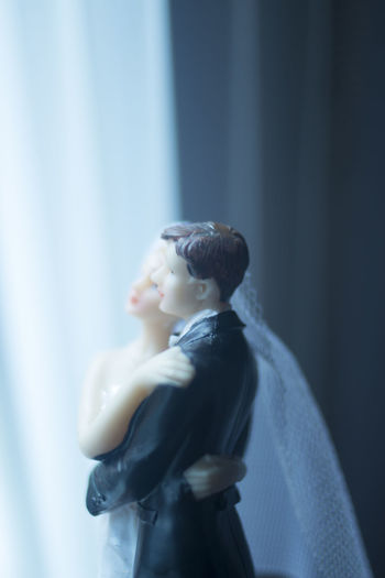 Close-up of wedding cake figurine on table by window at home