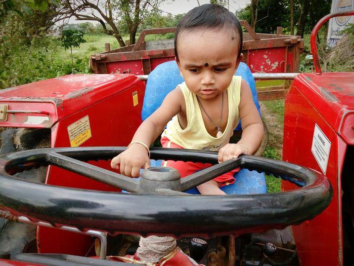 Baby boy sitting on tractor