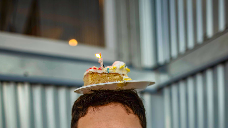 Close-up portrait of woman with cake and candle on head against blurred background