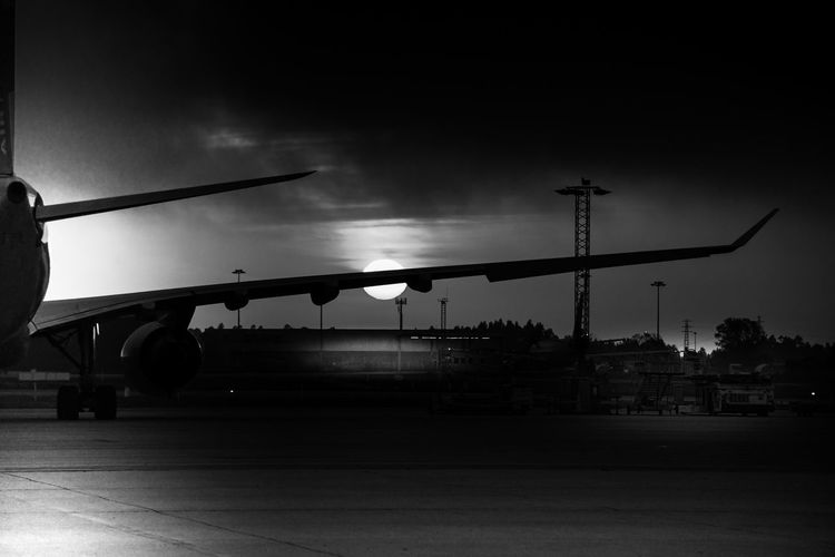 Silhouette airplane on airport runway against sky at dusk