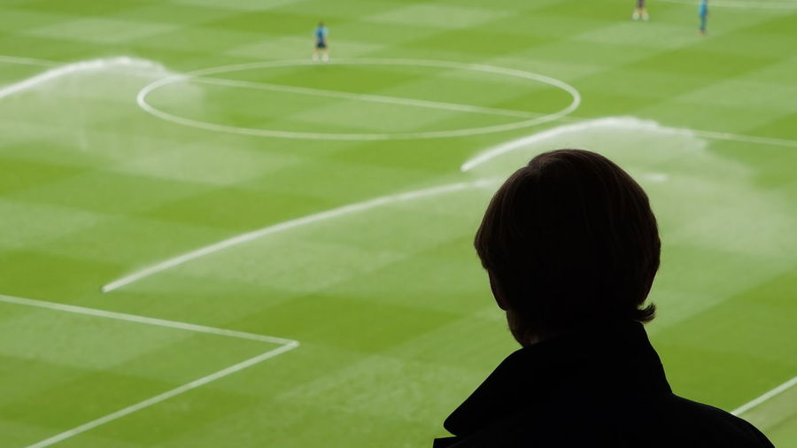 Rear view of man looking at football ground