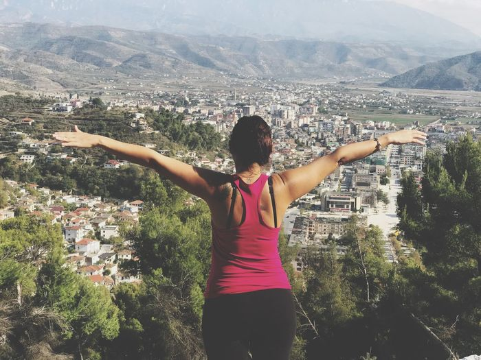 Rear view of woman with arms outstretched on mountain against cityscape