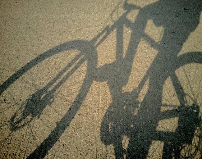 High angle view of shadow of bicycle on road