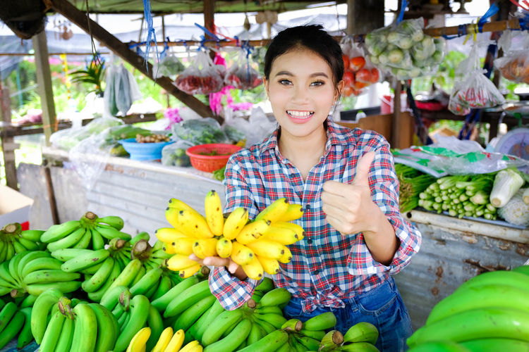 Portrait of smiling young woman standing at market stall