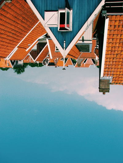 Upside down image of houses against sky