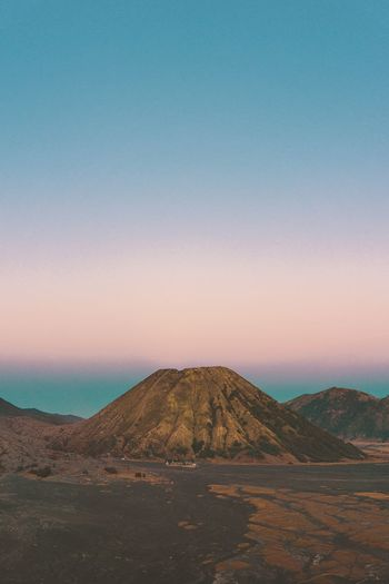 Scenic view of arid landscape against clear sky during sunset