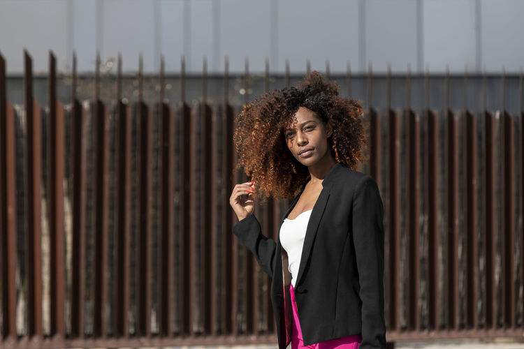 Young woman with curly hair standing against wall