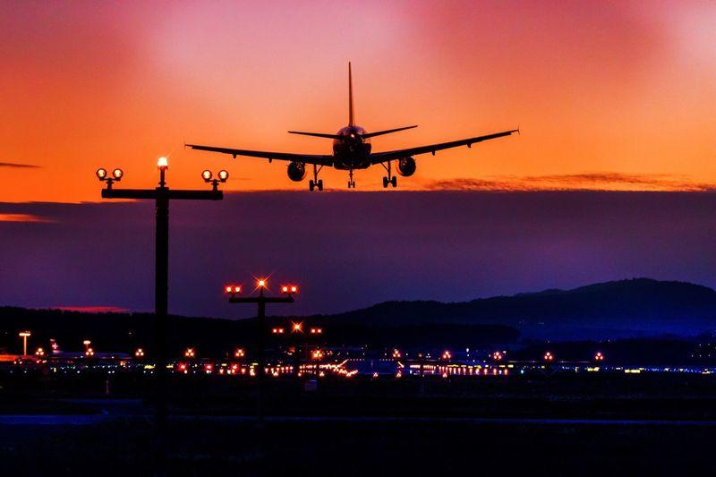 Airplane landing at airport against orange sky