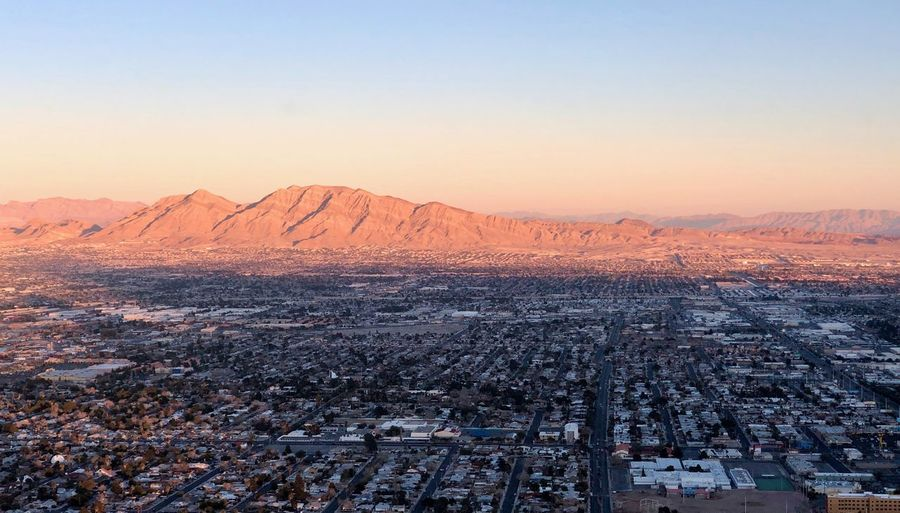 Aerial view of city by mountain against clear sky