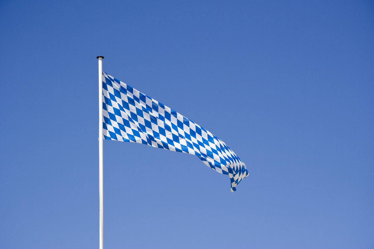 Low Angle View Of Bavarian Flag Against Clear Blue Sky During Sunny Day