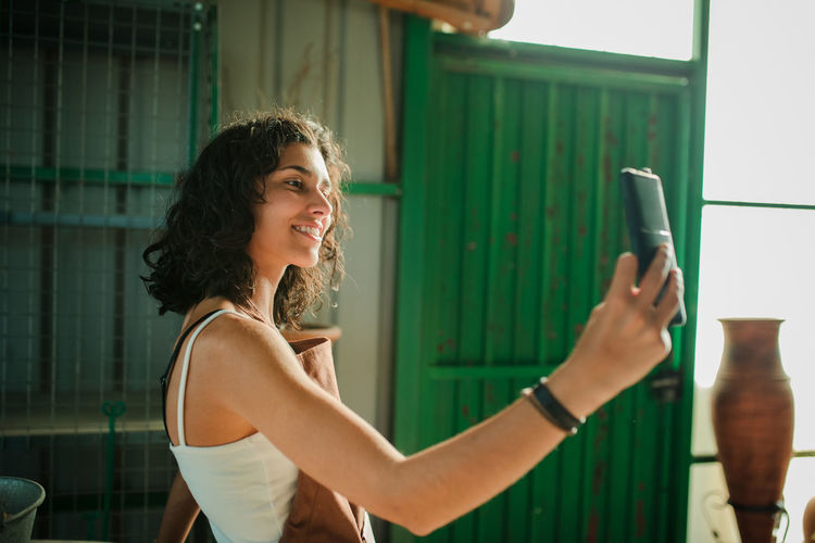 Smiling young woman taking selfie with mobile phone while standing against wall