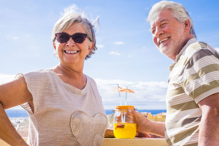 Happy senior couple having drink while standing against sky