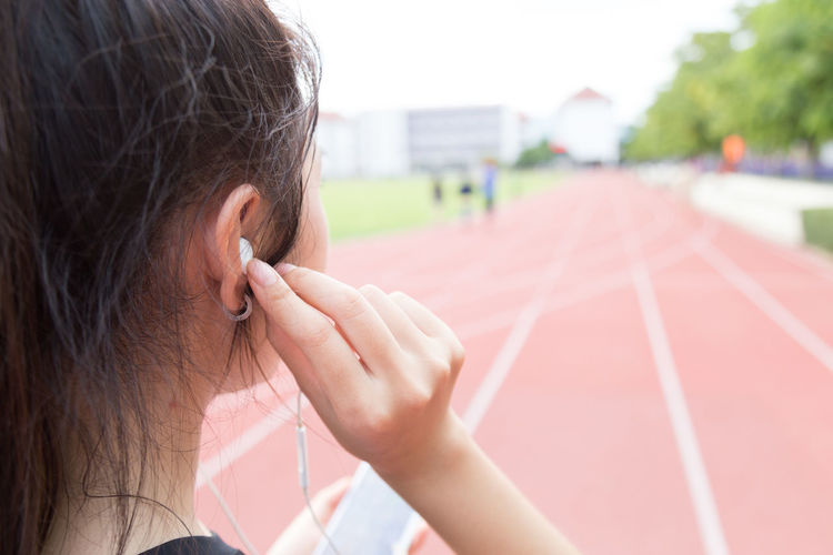 Close-up of athlete listening to music on headphones at running track