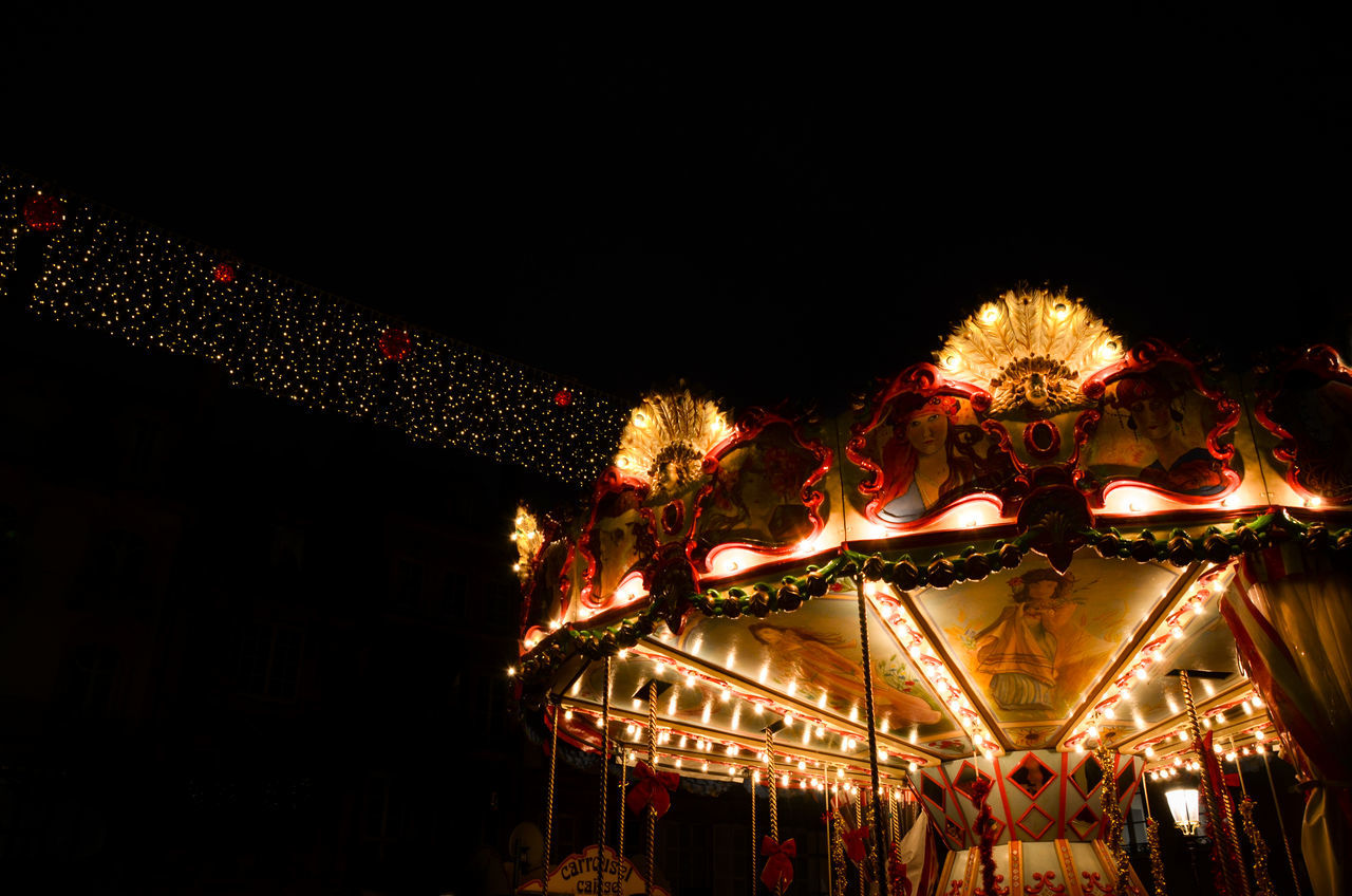 amusement park, arts culture and entertainment, night, illuminated, carousel, amusement park ride, enjoyment, leisure activity, carousel horses, outdoors, low angle view, no people, merry-go-round, nightlife, clear sky, sky