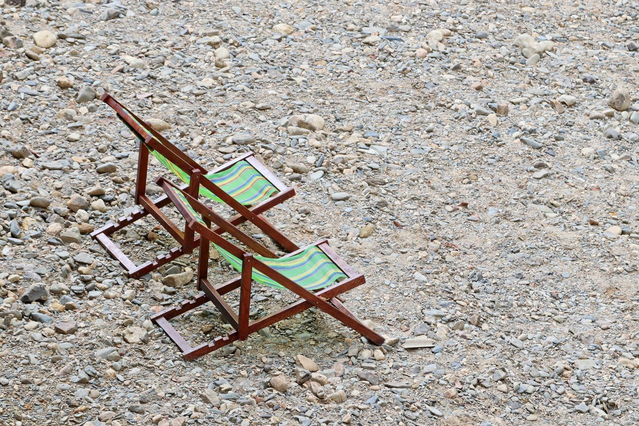 HIGH ANGLE VIEW OF EMPTY CHAIR ON TABLE BY FIELD