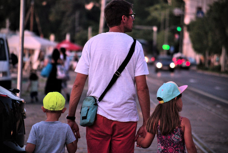 Fatherhood  Father And Children Traffic Lights Family Adult Casual Clothing Child City City Life Day Evening Walk Focus On Foreground Group Of People Incidental People Leisure Activity Lifestyles Men People Real People Rear View Street Togetherness Walking