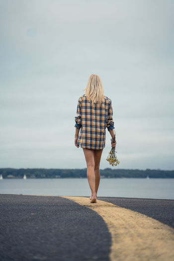 Rear view of woman holding flowers while walking on road