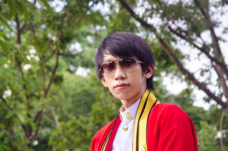 Young man handsome smile cosplay is Prince Standing under the shade Elegant gesture wearing black glasses. Asian  Cosplay Handsome Man Adult Asain Architechture Asian Man Black Hair Cosplayer Day Handsome Handsome Boy Handsome Guy  Headshot Looking At Camera Model Nature One Person Outdoors People Portrait Real People Smile Sunglasses Tree Young Adult