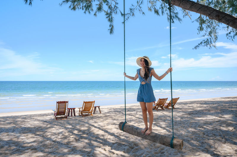 Full length of woman on chair at beach against sky