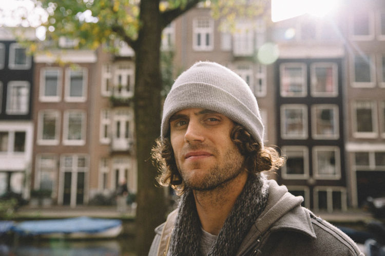 Portrait Of Man Wearing Knit Hat With Buildings In Background