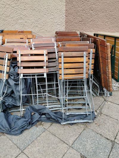 High angle view of chairs on footpath against wall