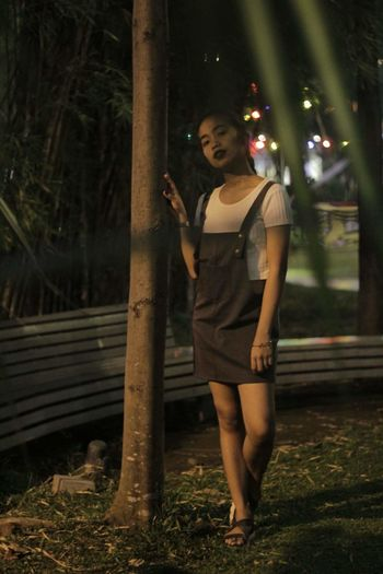 Full length portrait of young woman standing by tree trunk at night