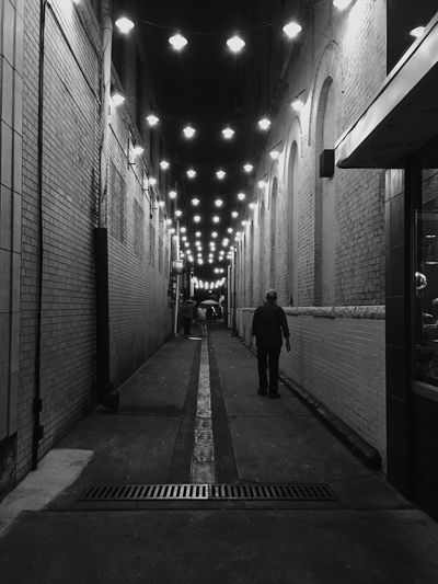 Rear view of man walking on illuminated corridor