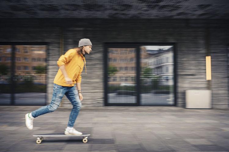 Full length of man skateboarding on street
