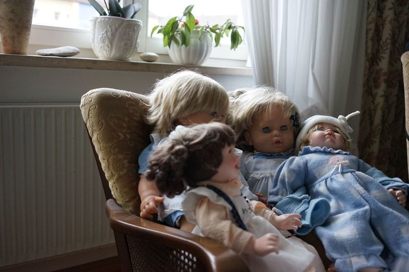 Dolls on chair at home