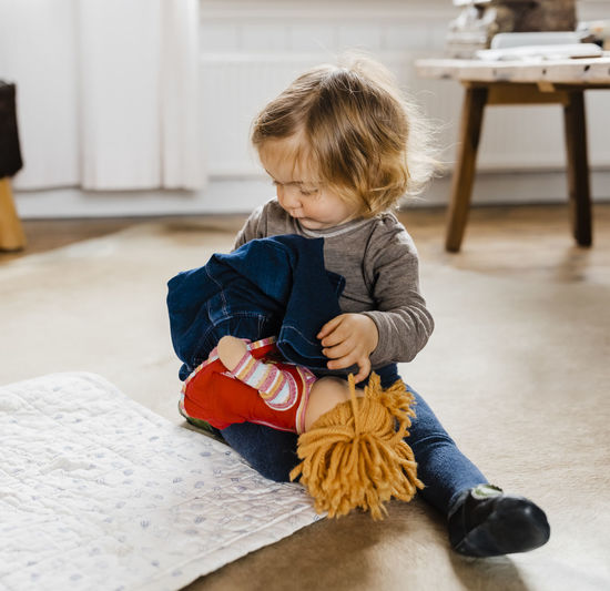 Girl playing with doll while sitting at home
