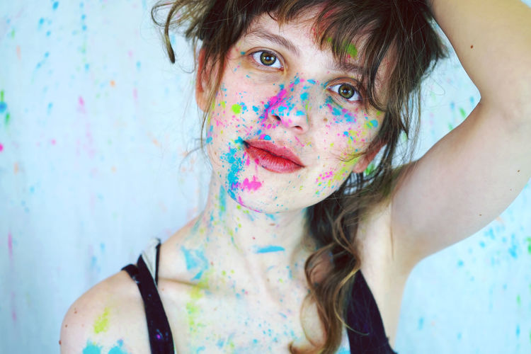 Close-up portrait of young woman covered in powder paint with brown hair