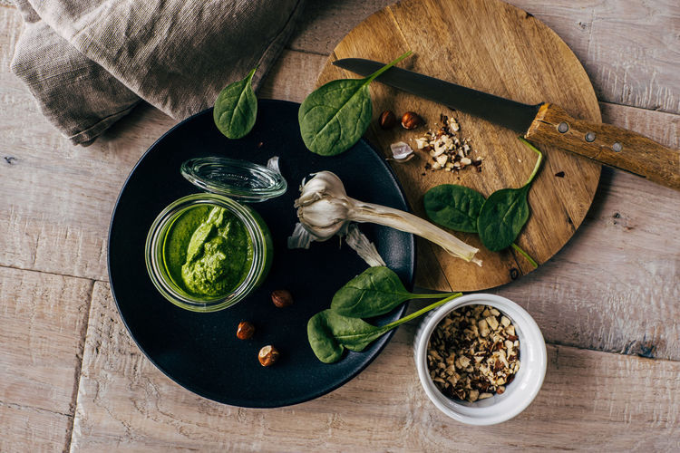 High angle view of served pesto sauce with garlic on table
