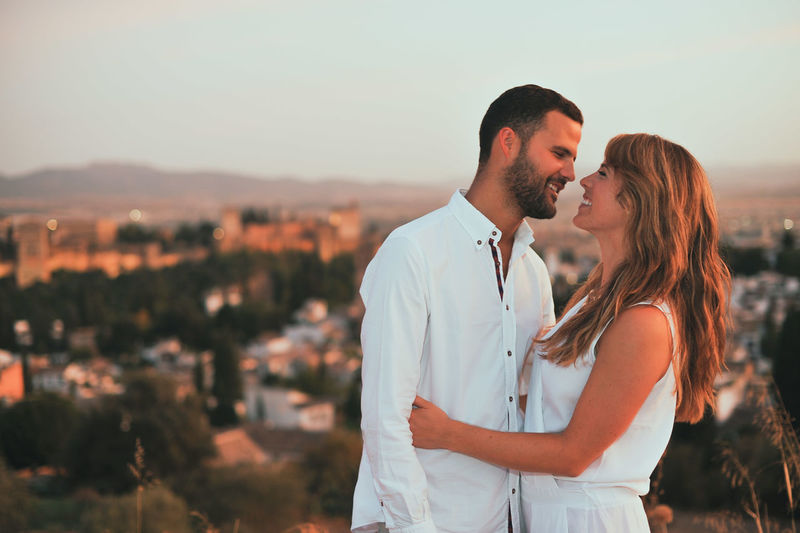 Smiling couple standing against cityscape during sunset