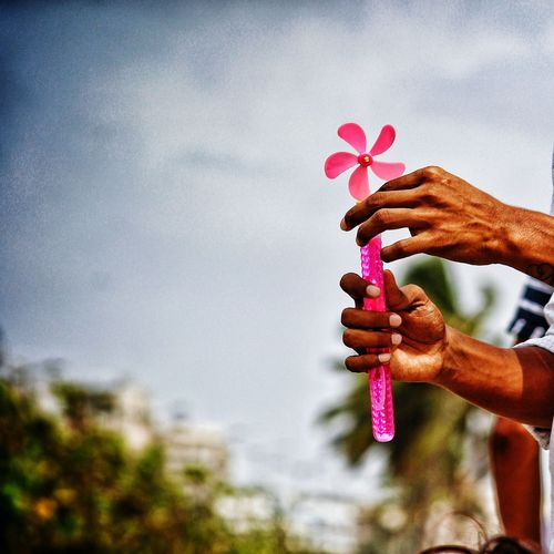 Midsection of man holding pinwheel toy against sky