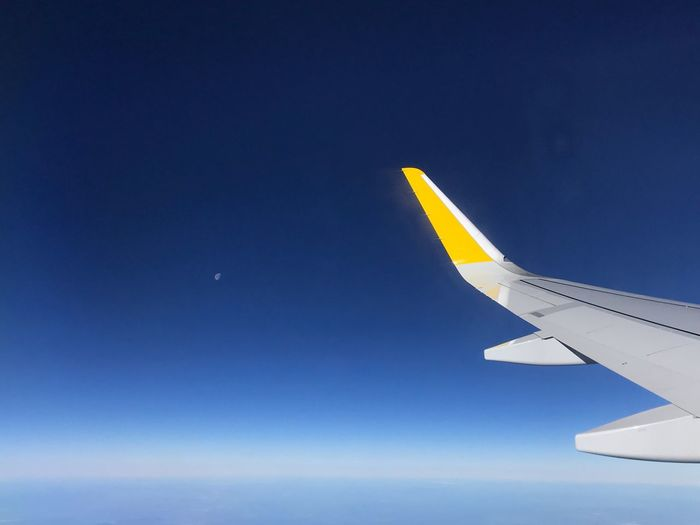 Cropped image of airplane wing flying against clear blue sky