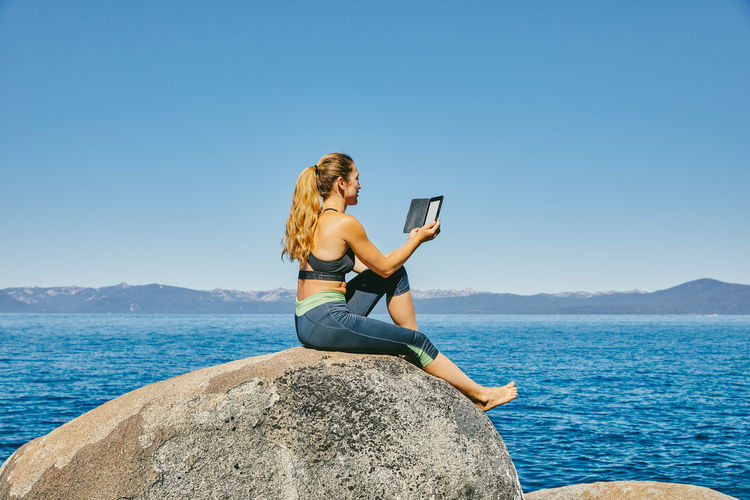 Man using mobile phone while sitting on rock against sea
