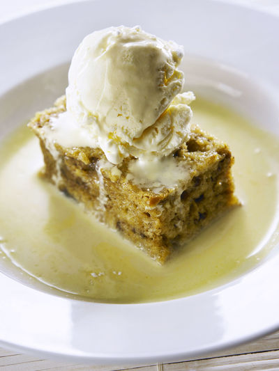 sticky date pudding with ice cream on top Puddling Close-up Crockery Dairy Product Date Puddling Dessert Food Food And Drink Freshness Frozen Frozen Food Ice Cream Indoors  Indulgence Melting No People Plate Ready-to-eat Still Life Sweet Sweet Food Table Temptation Unhealthy Eating Vanilla Ice Cream